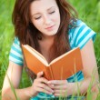 Young woman sits on grass and reading book — Stock Photo #9899640