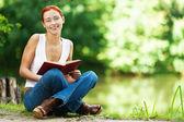 Bella donna seduta sul terreno con libro — Foto Stock
