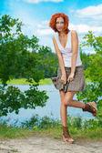 Bella donna in piedi vicino al lago — Foto Stock