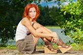 Bella donna seduta sulla riva del lago — Foto Stock