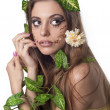 Beautiful young woman with flowers, leaves in her hair and origi — Stock Photo