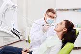 Diş hekimi diş hasta muamelesi yapıyor — Stok fotoğraf