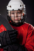 Portrait of a young ice hockey player on dark background — Stock Photo