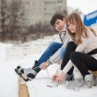 Stock Photo: Couple lacing up skates