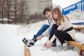 Couple lacing up the skates — Stock Photo
