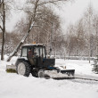 Small tractor snow removal in park - Stock Photo