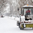 Snow removal a small tractor in the park - Stock Photo