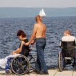 Stock Photo: Disabled in wheelchairs on the embankment