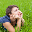 Stock Photo: Young Woman relaxing on the green grass