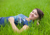 Young Woman relaxing on the green grass — Stock Photo