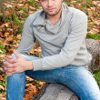 Outdoors portrait of happy young man sitting in autumn park — Stock Photo #10228044