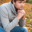 Outdoors portrait of happy young man sitting in autumn park — Stock Photo #10228046