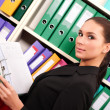 Business woman in front of shelves with folders — Stock Photo #10228078