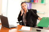 Business woman sitting in the office in front of the laptop and — Stock Photo