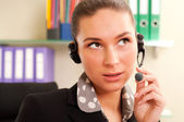 Young business woman wearing headphones — Stockfoto