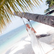 Beautiful bride swinging on tropical sea side background — Stock Photo #10475195