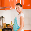 Beautiful young woman cooking in the kitchen — Stock Photo #10475198