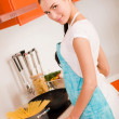 Beautiful young woman cooking in the kitchen — Stock Photo #10475199