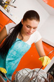 Woman cleaning kitchen using dish washing machine — Stock Photo