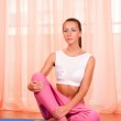 Portrait of pretty young woman doing yoga exercise on mat — Stock Photo #8191647