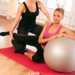 Trainer helping woman in doing exercise on ball — Stock Photo