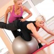 Stock Photo: Trainer helping woman in doing exercise on ball
