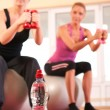 Bottle of water in front of group of doing fitness exerci — Stock Photo #8499115