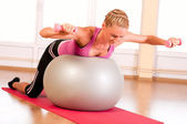 Young woman in sportswear, doing fitness exercise with fit ball — Stock Photo