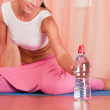 Young woman sitting on a yoga mat and holding bottle of water — Stock Photo