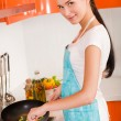 Beautiful young woman cooking in the kitchen — Stock Photo #8624055