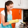 Attractive brunette woman cleaning kitchen using dish washing ma — Стоковое фото