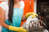 Attractive brunette woman cleaning kitchen using dish washing ma — Stock Photo