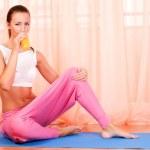 Young woman sitting on a yoga mat drinking orange juice — Stock Photo
