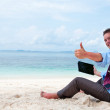 Business man sitting and working on the beach with tablet comput — Stock Photo #9450589