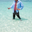 Funny business man calling by cell phone on the beach — Stock Photo