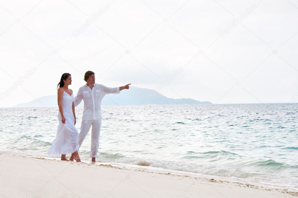 Picture of romantic young couple having a walking on the sea shore  Foto de Stock   #9450563
