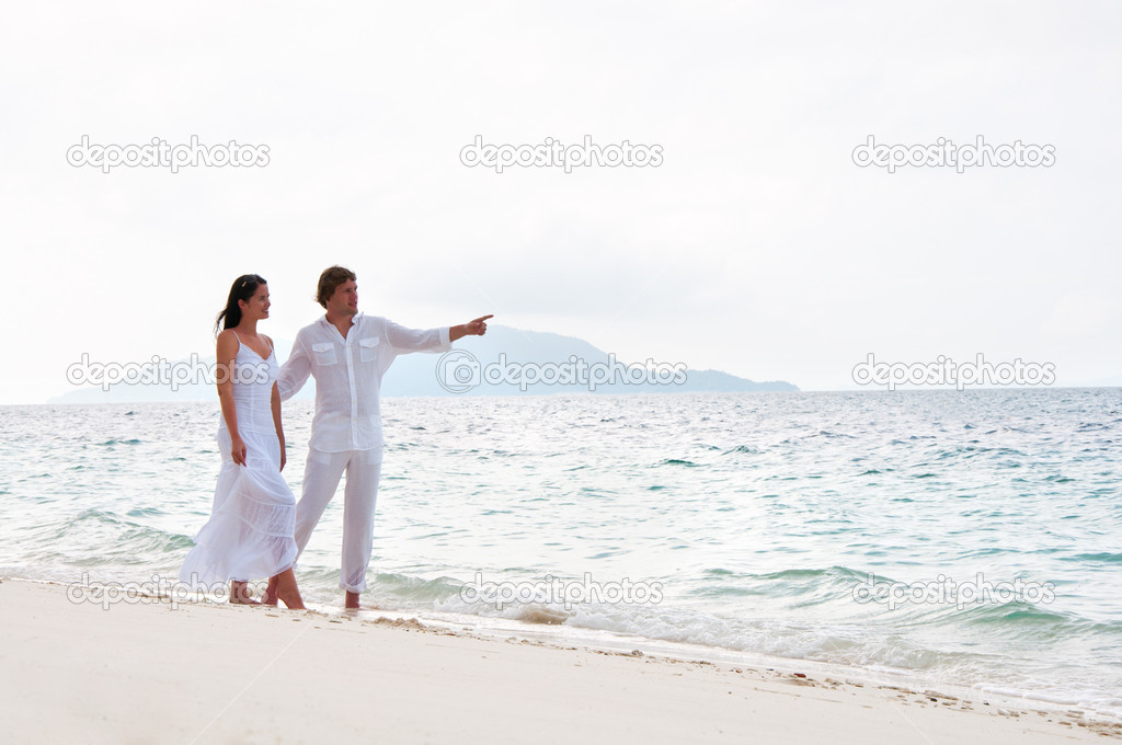 Picture of romantic young couple having a walking on the sea shore  Stock Photo #9450563