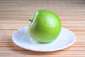 Green apple on the saucer — Stock Photo