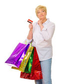 Happy senior woman with bags and credit card — Stock Photo