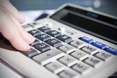 Hand touching calculator in office — Stock Photo