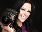 Smiling photographer woman holding camera over dark — Stock Photo