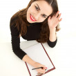 Young woman writing on clipboard - Stock Photo