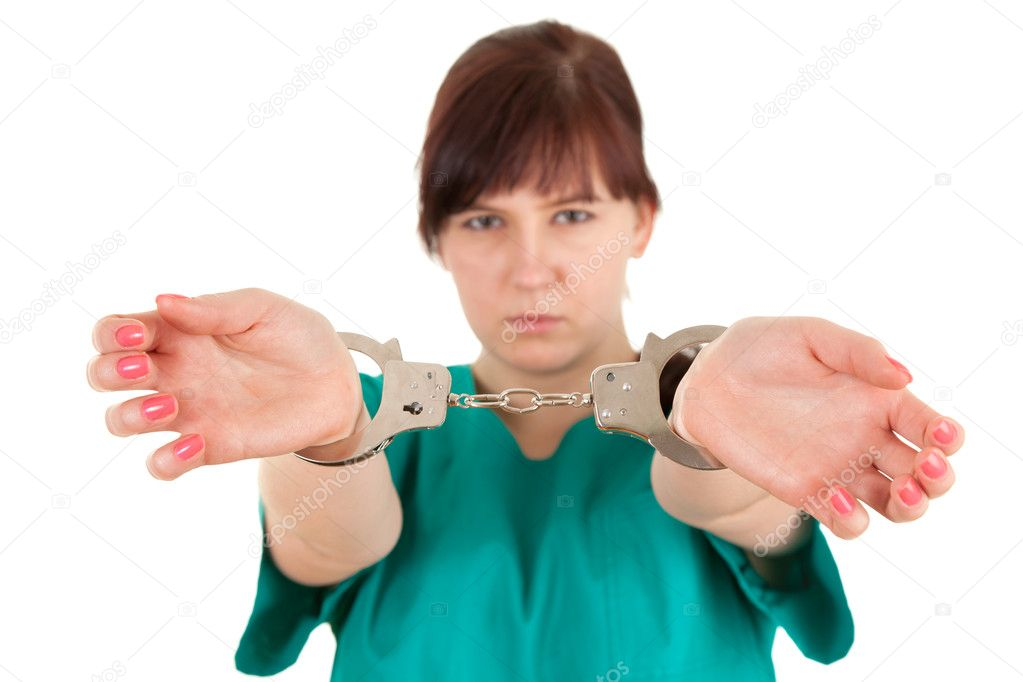 Frightened  lady doctor in green uniform with handcuffed hands, focus on foreground, white background  Stock Photo #10402848