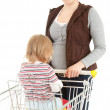 Smiling mother with baby in trolley — Stock Photo