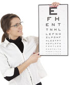 Young woman in glasses, with eye chart — Stock Photo