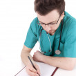 Male doctor writing on clipboard - Stock Photo