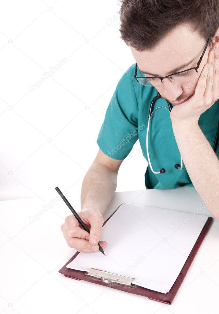 Male doctor writing on clipboard sitting at desk, white background  Stock Photo #9759847