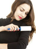 Girl cleaning dust with lint roller — Stock Photo