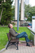 Homeless drunk man sleeping on the bench hot day — Stock Photo