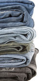 Lot of blue jeans isolated on white — Stock Photo